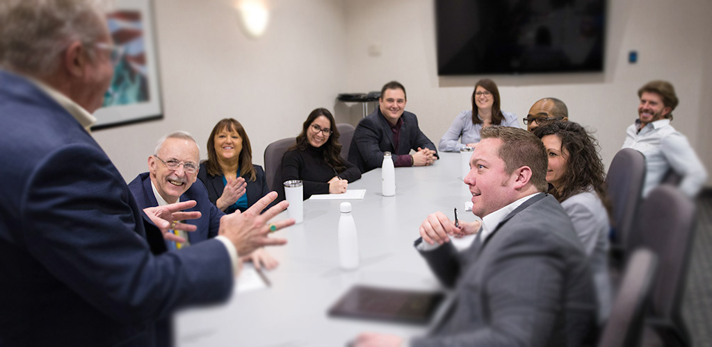 a team meeting with various people sitting at a long table